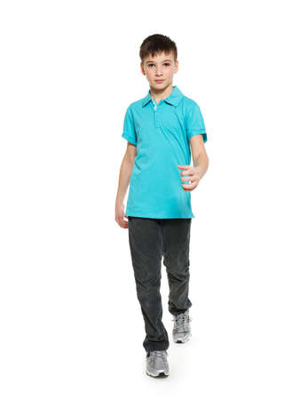 casuals: Full portrait of walking teen boy in blue t-shirt casuals  isolated on white background.