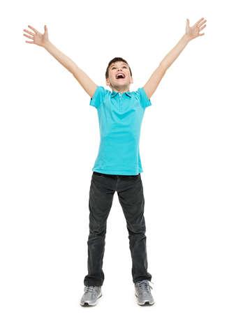 niño parado: Muchacho adolescente joven feliz con en casuals con las manos levantadas hacia arriba sobre fondo blanco.