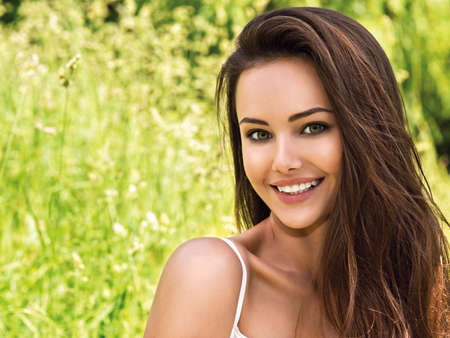 summer beauty: portrait of the young beautiful smiling woman outdoors