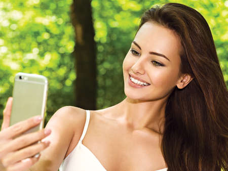 summer beauty: beautiful young woman selfie in the park with a smartphone