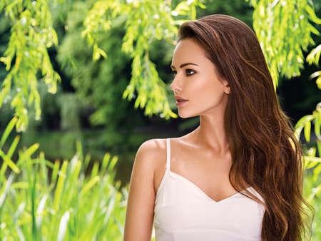 profil: Portret młodej pięknej kobiety z długimi włosami. na dworze.