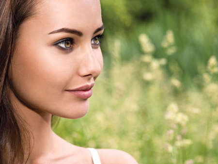 profile face: portrait of the young beautiful woman with long hairs. outdoors. Stock Photo