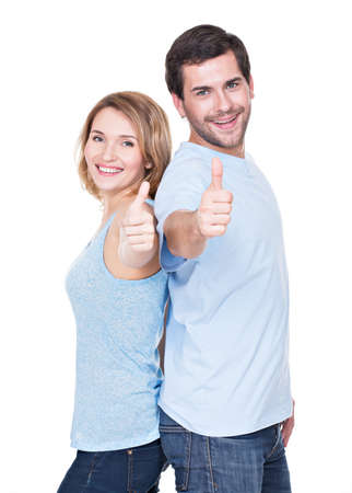 白い背景で隔離のサインを親指で幸せなカップルの肖像画。 写真素材