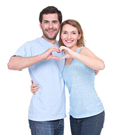 alzando la mano: Retrato de alegre sonriente pareja de pie juntos muestran corazón manos - aislado en fondo blanco.