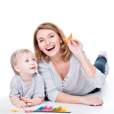 aucasian: Portrait of happy mother playing with little child lying - isolated on white.