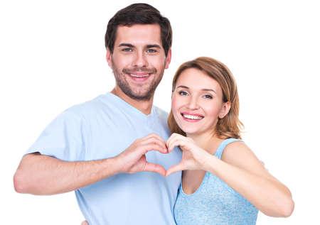 alzando la mano: Retrato de alegre sonriente pareja de pie juntos muestran coraz�n manos - aislado en fondo blanco.