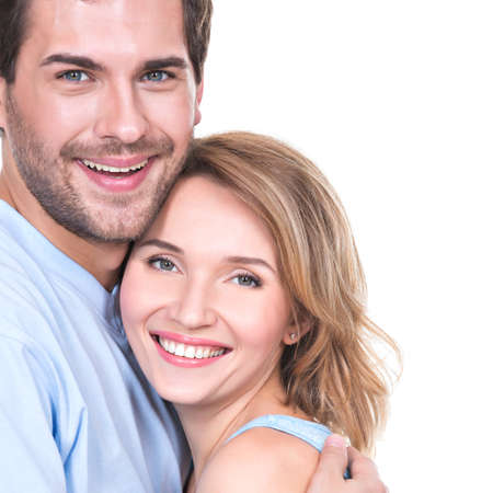 young couple smiling: Portrait of happy young couple in embrace standing on white background.