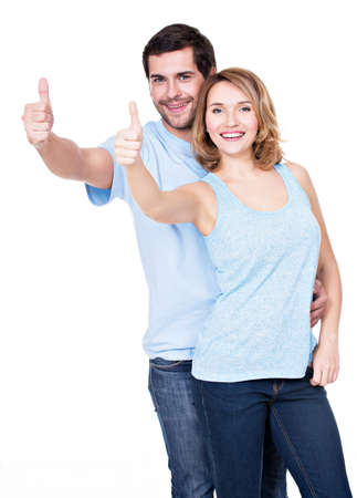 Portrait of happy couple with thumbs up sign isolated on white background. photo