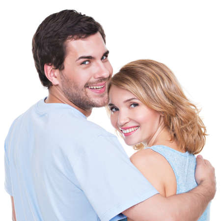 Back view of young couple in embrace standing on white background. photo