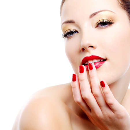 Close-up portrait of sexy caucasian young woman with golden glamour make-up and red bright manicure photo