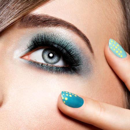 青緑色のメイクと女性の目。長い付けまつ毛。マクロ撮影