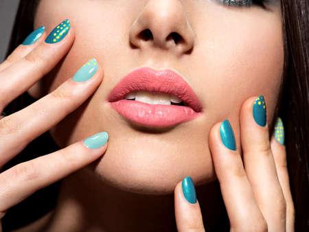 azul turqueza: Dedos de la mujer con color azul motton de las uñas en la cara