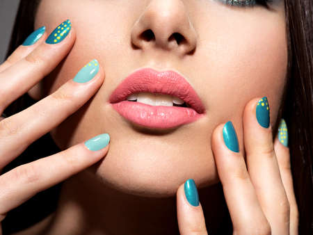 motton blue: Womans fingers with motton blue color of the nails on the face Stock Photo