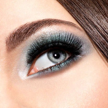 false eyelashes: womans eye with turquoise makeup. Long false eyelashes. macro shot