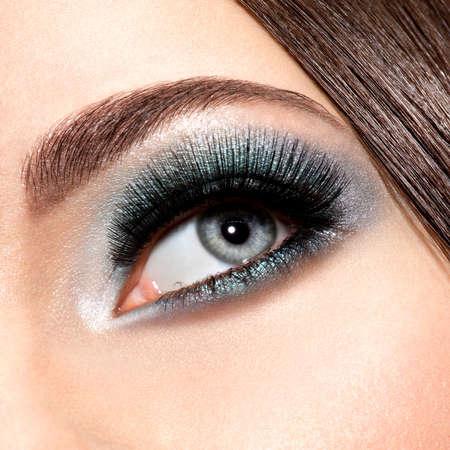 motton: womans eye with turquoise makeup. Long false eyelashes. macro shot
