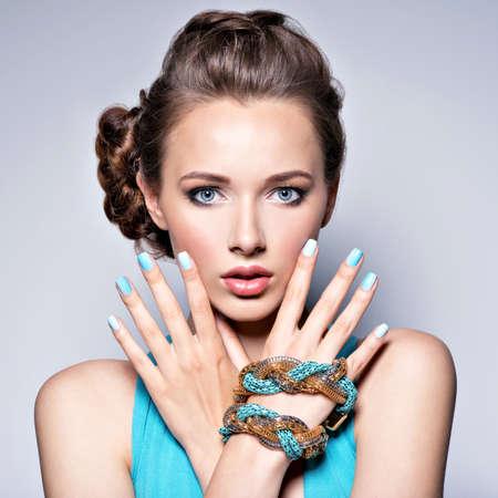 ジュエリーの若い美しい女性。宝石類を身に着けている青いドレスの女の子のファッション。青い爪が魅力的なモデル。 写真素材