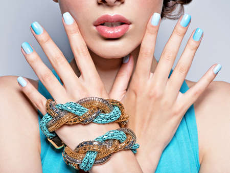 fashion jewellery: woman hands nails manicure fashion blue jewelry. Female hands with blue fingernails
