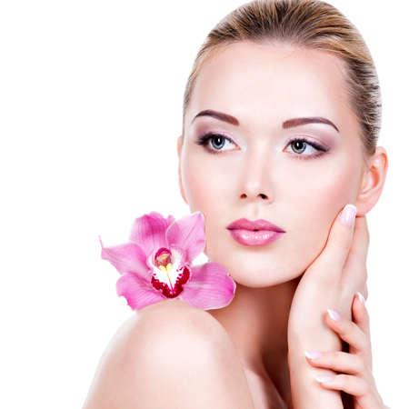 maquillaje de ojos: La cara del primer de una mujer hermosa joven con un maquillaje de ojos púrpura y labios. Muchacha adulta bonita con la flor cerca de la cara. - Aisladas sobre fondo blanco
