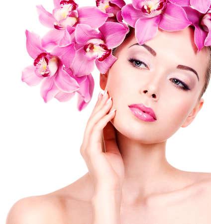 le visage Gros plan d'une belle jeune femme avec un maquillage et des lèvres des yeux violet. adulte fille Jolie fleur près du visage. - Isolé sur fond blanc