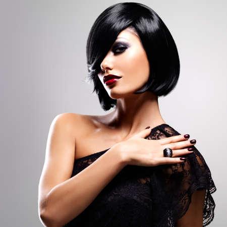 modelos posando: Hermosa mujer morena con el peinado de tiro, retrato del primer de un modelo femenino Foto de archivo