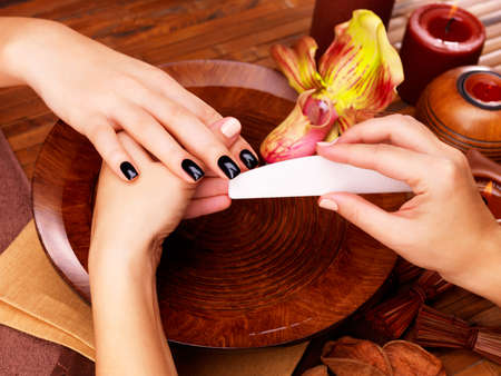 womans hands: Manicurist master  makes manicure on womans hands - Spa treatment concept