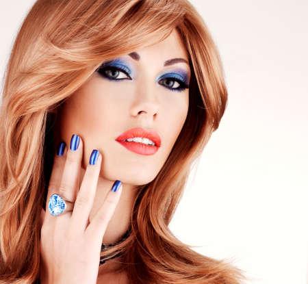Primer de la cara de una mujer hermosa sensual con las uñas azules, azules de maquillaje y los labios rojos atractivos en el fondo blanco