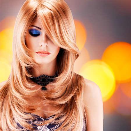 luz roja: mujer bonita hermosa con los pelos largos de color rojo. Retrato de modelo de moda joven con el maquillaje de ojos azules