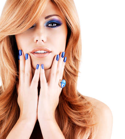 color hair: portrait of a beautiful woman with blue nails, blue makeup and  long red hairs  on white  background Stock Photo