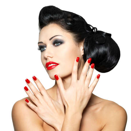 labios rojos: Mujer hermosa de la manera con los labios rojos, clavos y el peinado creativo - aislado en fondo blanco Foto de archivo