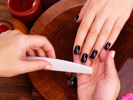 master: Manicurist master  makes manicure on womans hands - Spa treatment concept