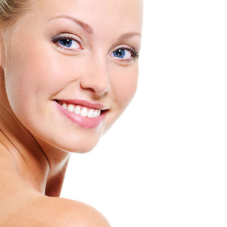 Woman face with a nice smile and healthy beautiful clear skin over white backgrouns photo
