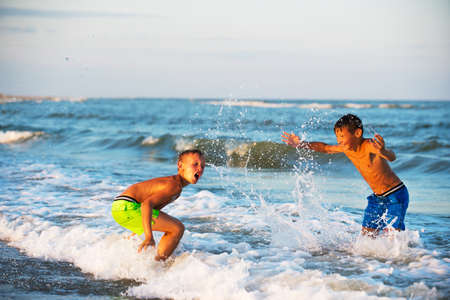 boys playing: Two boys playing at the beach with water. Big splashes