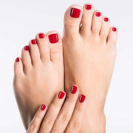 photo Gros plan d'un pieds féminins avec une belle pédicure rouge sur fond blanc