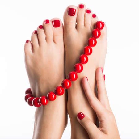 Detailní fotografie ženské nohy s krásným červeným pedikúry a velké korálky - na bílém pozadí