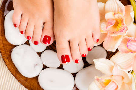 Closeup photo of a beautiful female feet with red pedicure Reklamní fotografie - 53558741