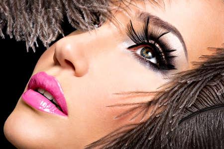 Bella donna con brillante make-up professionale con piume vicino al viso.
