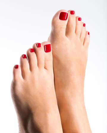 beautiful feet: Closeup photo of a beautiful female feet with red pedicure isolated on white