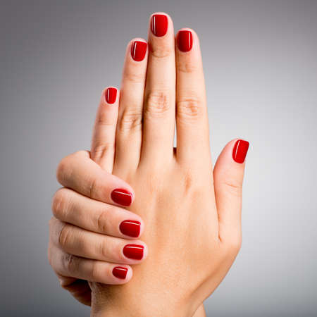 human fingernail: Closeup photo of a beautiful female hands with red nails Stock Photo