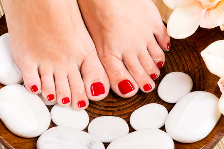Closeup photo of a beautiful female feet with red pedicure Фото со стока