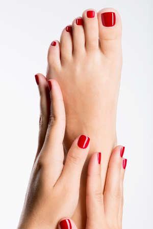 pedicura: Foto de cerca de un hermoso pies femeninos con pedicure rojo sobre fondo blanco Foto de archivo