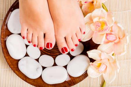 beautiful feet: Closeup photo of a beautiful female feet with red pedicure Stock Photo