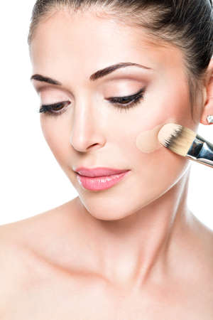 applying: Makeup artist applying liquid tonal foundation  on the face of the woman