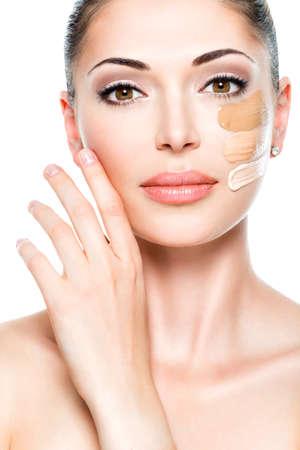 Hermoso rostro de mujer joven con la fundación de cosmético en la piel. Concepto de tratamiento de belleza