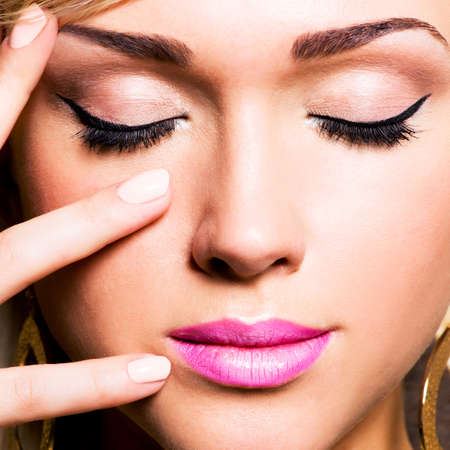 pink nails: Closeup  pretty face of a caucasian woman with black eyelashes