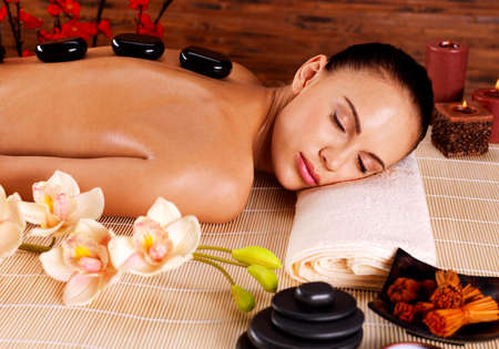 spa therapy: Adult woman relaxing in spa salon with hot stones on back. Beauty treatment therapy Stock Photo