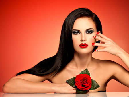 long hairs: Portrait of a beautiful woman with red lips,  nails and rose in hand.  Pretty adult girl holding red rose in hands. Fashion model with long hairs posing at studio over red background