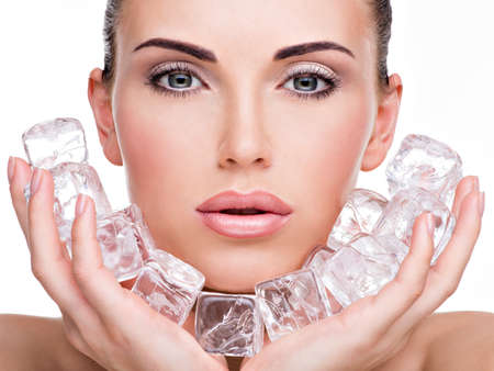 ice: Beautiful young woman applies the ice to face. Skin care concept.