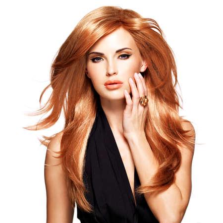 Mooie vrouw met lange rechte rood haar in een zwarte jurk aan te raken haar gezicht. Fashion model poseren in de studio. Geïsoleerd op wit