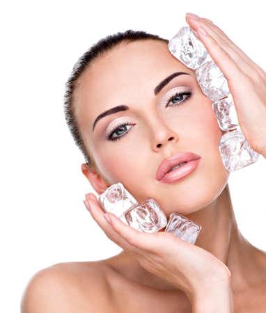美しい若い女性は、顔に氷を適用されます。肌ケアのコンセプトです。 写真素材