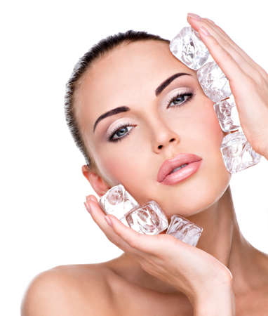 Beautiful young woman applies the ice to face. Skin care concept.